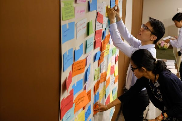 Two individuals add post it notes to a wall of colorful post it notes
